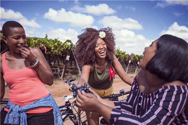 Three women eating grapes in a vineyard with their bicycles